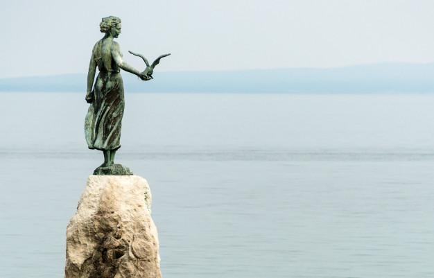 maiden-girl-holding-seagull-facing-sea-statue-rocks-opatija_105811-116